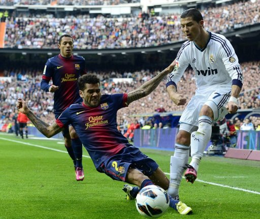 Real Madrid's Cristiano Ronaldo clashes with Barcelona's Dani Alves in Madrid on March 2, 2013