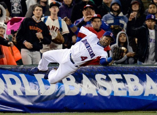 Miguel Tejada of the Dominican Republic dives to make a catch at the World Baseball Classic on March 19, 2013