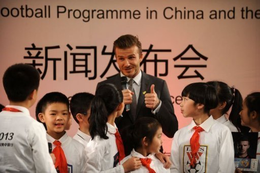 David Beckham (C) answers questions from a group of pupils at a primary school in Beijing on March 20
