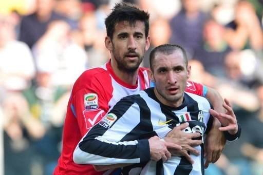 Juventus' Giorgio Chiellini is held by Catania defender Nicolas Spolli during the sides' Serie A match on March 10, 2013