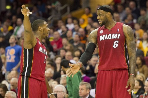 Mario Chalmers (L) and LeBron James discuss a play against the Cleveland Cavaliers on March 20, 2013