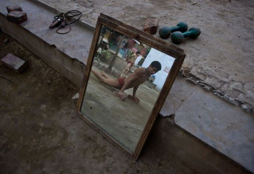 A budding Indian wrestler does push-ups  at a traditional mud akhara in New Delhi on March 6, 2013