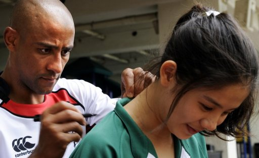 Australian rugby legend George Gregan signs the back of a fan's jersey in Hong Kong on March 22, 2011