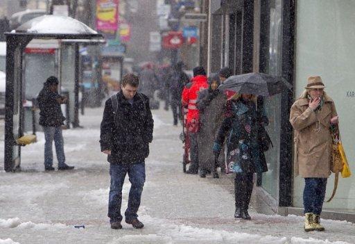 Pedestrians walk through the snow in Belfast City centre in Northern Ireland, on March 22, 2013