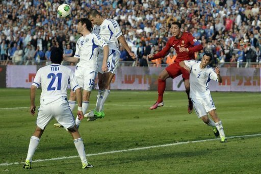 Portuguese forward Cristiano Ronaldo (R) goes up for a high ball against a packed Israel defence on March 22, 2013