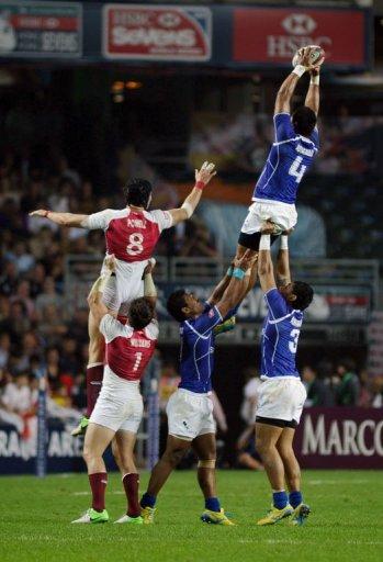 Samoa's Faatoina Autagavaia (upper R) controls the ball against England's players on March 22, 2013