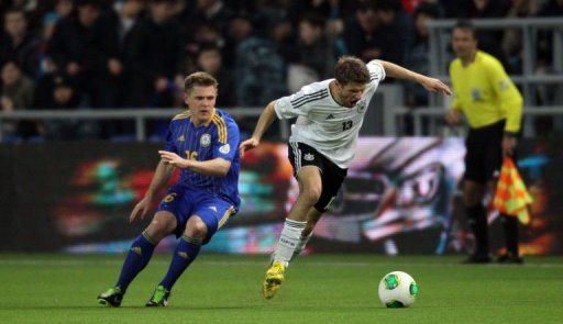 Germany's Thomas Muller (R) clashes with Kazakhstan's Heinrich Schmidtgal in Astana, March 22, 2013