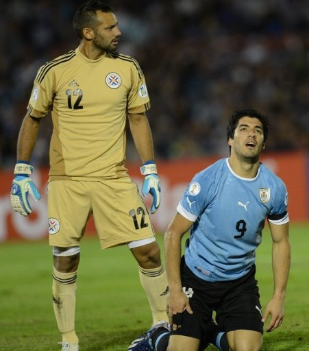 Uruguay's Luis Suarez (R), seen next to Paraguay's goalkeeper Diego Barreto, in Montevideo, on March 22, 2013