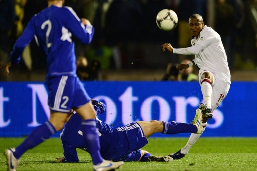 England's Ashley Young shots past San Marino's  Alex Gasperoni in their World Cup 2014 qualifying match March 22, 2013