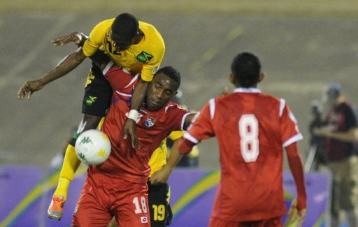 Jamaica's Demar Phillips (top) fouls Panama's Alex Rodriguez at the National Stadium March 22, 2013, in Kingston