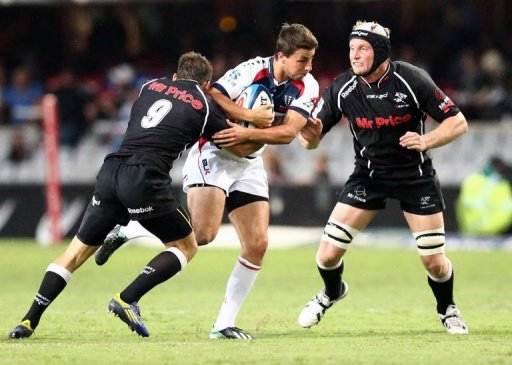Nick Phipps of the Rebels (C) is tackled by Cobus Reinach (L) and Franco van der Merwe (R) of the Sharks, March 23, 2013