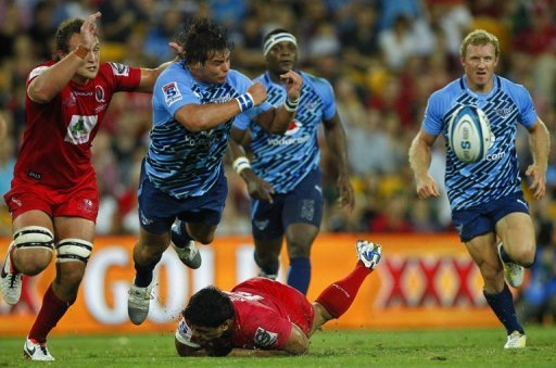 Northern Bulls' Johannes Engelbrecht gets a pass away as he is tackled by Queensland Reds' Ben Tapuai, on March 23, 2013