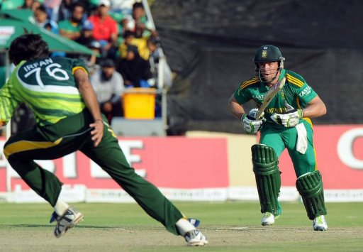 AB de Villiers (R) looks on as Mohammad Irfan (L) tries to catch him out in Benoni on March 24, 2013