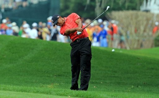 Tiger Woods plays his second shot at the par 4, 1st hole on March 24, 2013 in Orlando, Florida