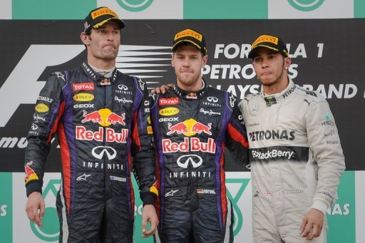 Sebastian Vettel (C) at the podium with second-placed Mark Webber (L) and third-placed Lewis Hamilton on March 24, 2013