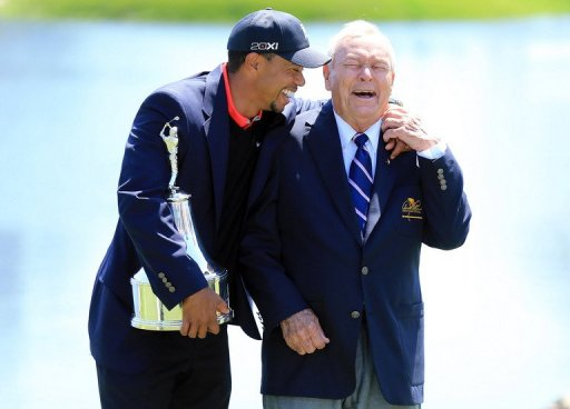 Tiger Woods (L) is presented with the trophy by Arnold Palmer at Bay Hill Golf and Country Club on March 25, 2013