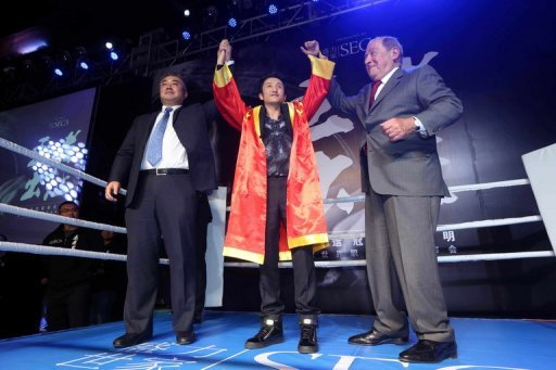 Zou Shiming (C) is pictured after signing with US promoter Bob Arum (R) during a ceremony in Beijing on January 23, 2013