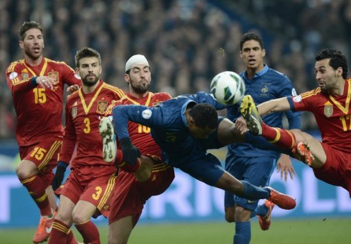 France defender Patrice Evra heads the ball away from the stretching Alvaro Arbeloa on March 26, 2013