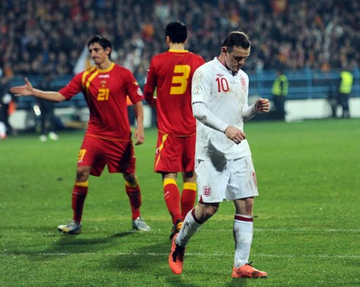 England forward Wayne Rooney (R) trudges off after the draw at Montenegro on March 26, 2013
