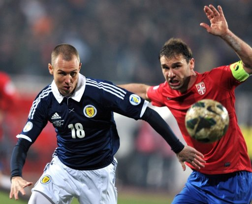 Kenny Miller (L) battles with Branislav Ivanovic during their World Cup qualifier on March 26, 2013