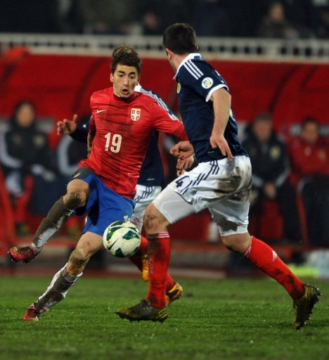 Serbia's Filip Djuricic (L) runs at the Scotland defence on March 26, 2013