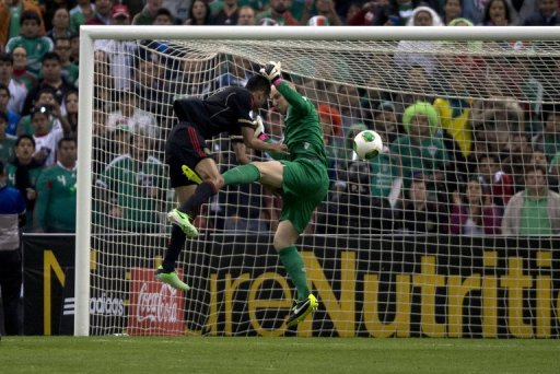 Mexico's Jesus Zavala (L) is denied by USA goalkeeper Brad Guzan during the World Cup qualifier on March 26, 2013