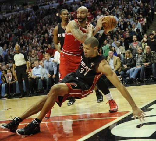 Shane Battier (R) of the Miami Heat falls to the floor under pressure from Carlos Boozer on March 27, 2013