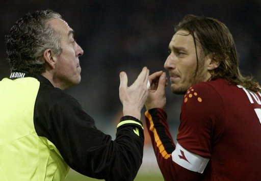 Francesco Totti (R) argues with the side referee during a Serie A match against Inter Milan on March 7, 2004