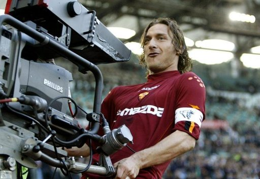 Francesco Totti celebrates with a TV camera after scoring at Rome's Olympic stadium on April 21, 2004