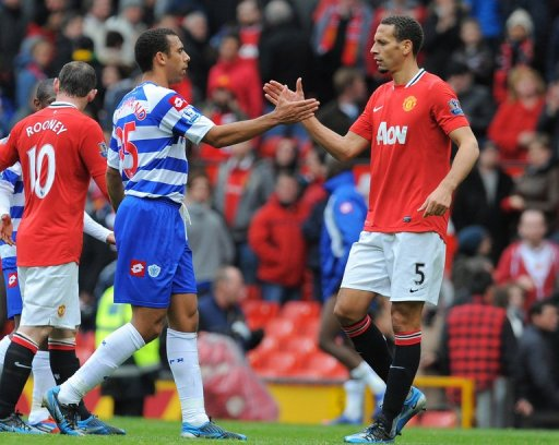 Anton Ferdinand shakes hands with brother Rio Ferdinand (R) at Old Trafford in Manchester, on April 8, 2012