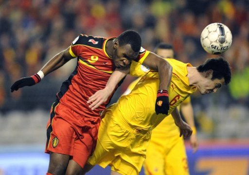 Belgium forward Christian Benteke (L) goes up for a header with Macedonia's Vance Sikov on March 26, 2013