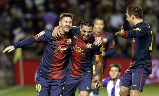 Barcelona's Xavi Hernandez (centre) celebrates with Lionel Messi after scoring against Valladolid on December 22, 2012