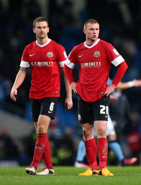 MANCHESTER, ENGLAND - MARCH 09:  Ryan Tunnicliffe and Stephen Foster of Barnsley look dejected at the final whistle after the FA Cup sponsored by Budweiser sixth round match between Manchester City and Barnsley at Etihad Stadium