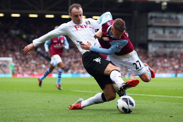 Dimitar Berbatov of Fulham is challenged by Joe Bennett of Aston Villa during the Barclays Premier League match between Fulham and Aston Villa at Craven Cottage on October 20, 2012 in London, England.  (Photo by Clive Rose/Getty Images)
