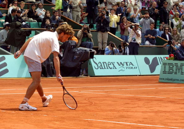 """This file picture taken on June 3, 2001 shows Brazilian Gustavo Kuerten drawing a heart on the court at the end of his fourth round match against US Michael Russell at the French Tennis Open in Roland Garros, Paris. Kuerten will play his last competition in 2008 at his home away from home, Roland Garros. Three-time French Open winner, """"Guga"""" won the hearts of Paris public for good in 2001 for a spontaneous gesture at the end of an extraordinary fourth round tie against American Michael Russell when he sunk to his knees and traced a huge heart with his racket on the red clay to dedicate his win to the fans in the stands. AFP PHOTO/FILES/JACQUES DEMARTHON TO GO WITH AFP STORY BY ALLAN KELLY (Photo credit should read JACQUES DEMARTHON/AFP/Getty Images)"""