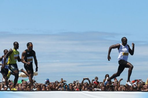 Jamaican runner Usain Bolt (R) competes in Copacabana Beach in Rio de Janeiro, Brazil, on March 31, 2013