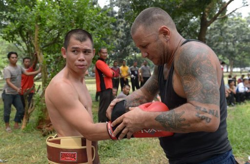 World featherweight champion Chris John is helped by coach Craig Christian during a training session on April 3, 2013
