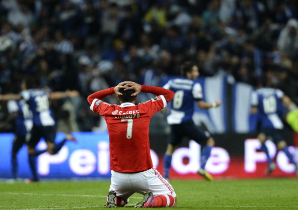 Benfica's Oscar Cardozo reacts as Porto's players celebrate after scoring during the Portuguese league  match FC Porto vs SL Benfica at Dragao stadium in Porto on May 11, 2013. (Getty Images)