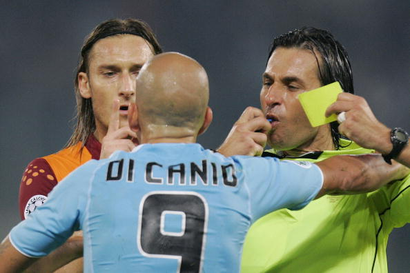referee Paparesta (R) gives the yellow card to Lazio's Paolo Di Canio, flanked by AS Roma's Francesco Totti during an Italian Serie A  match AS Roma-Lazio in Rome 23 October 2005. The match ended drawn 1-1.  (Photo credit should read CARLO BARONCINI/AFP/Getty Images)