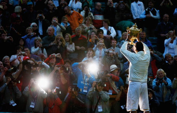 Rafael Nadal of Spain poses for photographers with the Championship trophy after winning the men's singles Final match against Roger Federer of Switzerland on day thirteen of the Wimbledon Lawn Tennis Championships at the All England Lawn Tennis and Croquet Club on July 6, 2008 in London, England.  (Photo by Pool/Getty Images)