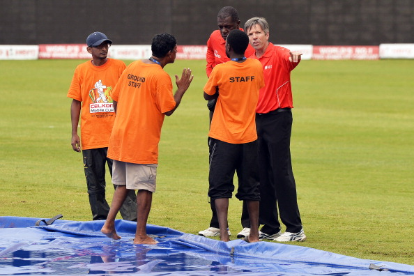 Match umpires Nigel Llong (R) and Peter Nero (2nd-R) talk to groundsmen as the review the field after a rain fall during the sixth match of the Tri-Nation series between India and Sri Lanka at the Queen's Park Oval stadium in Port of Spain on July 9, 2013. The match is at halt due to rain. (Getty Images)