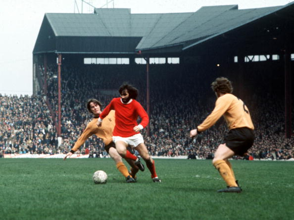 Football. Manchester United's George Best is tackled by Wolverhampton Wanderer's McCalliog from behind during their league match at Old Trafford, 1971.