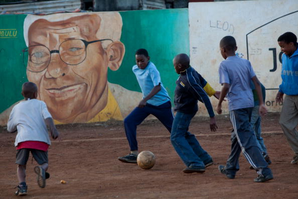 Children play football in front of a por
