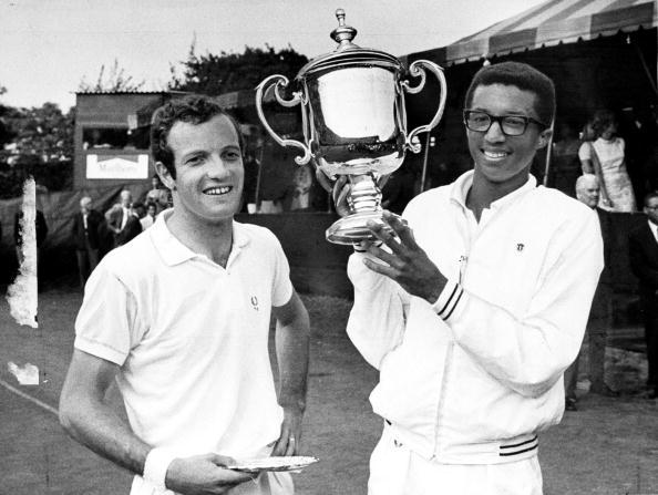 Arthur Ashe holds trophy after defeating Tom Okker (left), o