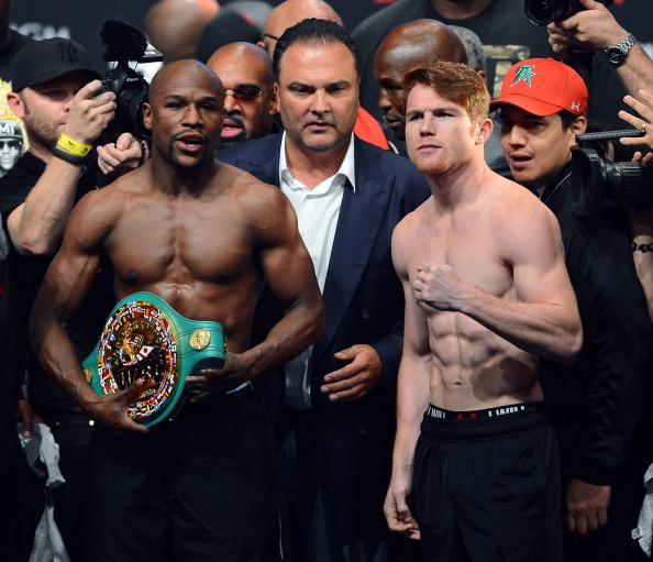 Floyd Mayweather Jr. (L) and Canelo Alvarez (R) pose during the official weigh-in for their bout at the MGM Grand Garden Arena