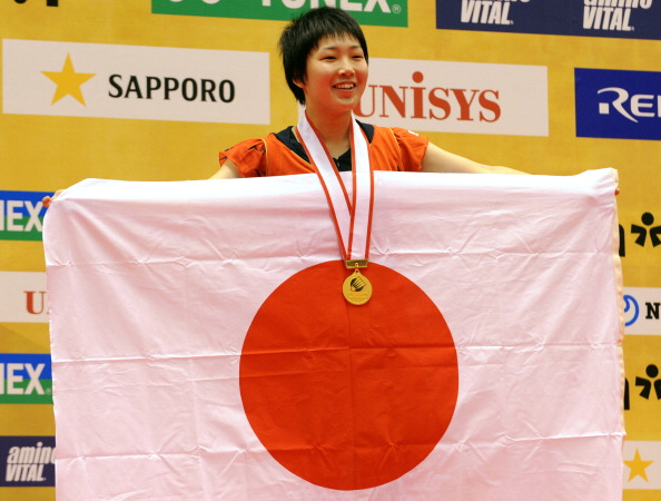 16-year-old Akane Yamaguchi of Japan (R) shows her national flag on the podium after her women's singles final at the Japan Open 2013 in Tokyo on September 22, 2013. (Getty Images)