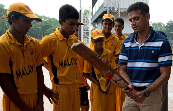 Former Indian cricket team skipper Rahul Dravid (R) teaches batting techniques to Malaysian U-16 cricketers during a training clinic in Kuala Lumpur on June 27, 2012.     AFP PHOTO / Saeed KHAN        (Photo credit should read SAEED KHAN/AFP/GettyImages)