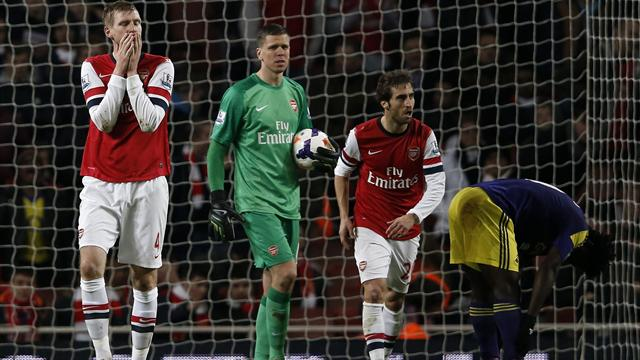 Arsenal's Per Mertesacker (L), Wojciech Szczesny (M) and Mathieu Flamini (L) are shocked at conceding the second goal against Swansea.