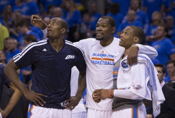 Serge Ibaka #9, Kevin Durant #35 and Russell Westbrook #0 of the Oklahoma City Thunder talk during the Memphis Grizzlies in Game One of the Western Conference Quarterfinals of the NBA Playoffs at Chesapeake Energy Arena on April 19, 2014 in Oklahoma City, Oklahoma