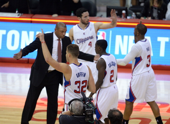 Los Angeles Clippers coach Doc Rivers (L) celebrates with players, from left, Blake Griffin (32), Darren Collison (2), J.J. Redick (4) and Chris Paul (30  at the NBA playoff game after the Clippers defeated the Golden State Warriors 113-103, April 29, 2014 at Staples Center in Los Angeles, California.
